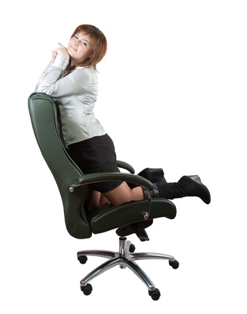 Young happy woman kneeling  on luxury office armchair, isolated over white background photo