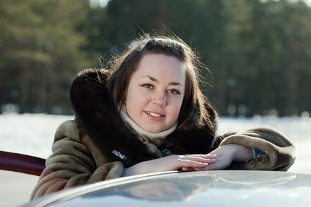Portrait of  young woman near her car in winter road Stock Photo - 12602359