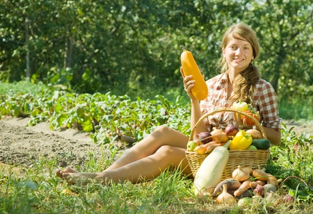 Gardener girl with basket of harvest in garden photo