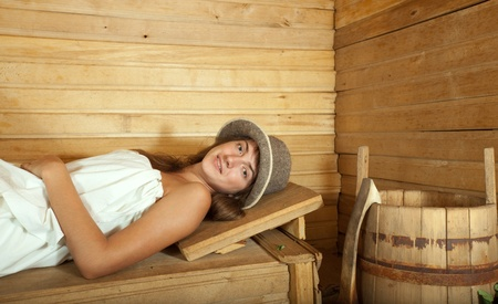 stive: Young girl relaxing on wooden bench in sauna   Stock Photo