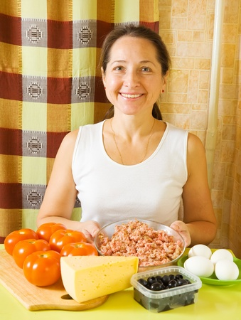 farci: Mature woman with ingredients for stuffed tomato in her kitchen. See in series stages of cooking of farci tomato
