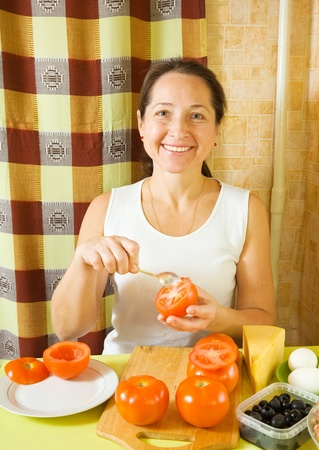 farci: Mature woman making stuffed tomato in her kitchen. See in series stages of cooking of stuffed tomato