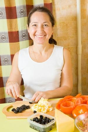 farci: Woman cutting olive on cutting board. See in series stages of cooking of farci tomato