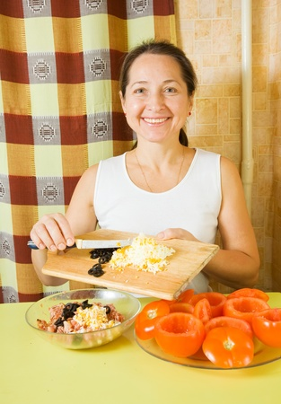 farci: Woman adds grated eggs and  sliced olives in mince. See in series stages of cooking of farci tomato