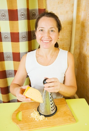 farci: Woman grating cheese. See in series stages of cooking of farci tomato