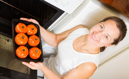 Mature woman roasting stuffed tomato  in oven.