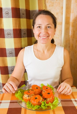 farci: Woman with baked stuffed tomato. See in series stages of cooking of stuffed tomato  Stock Photo