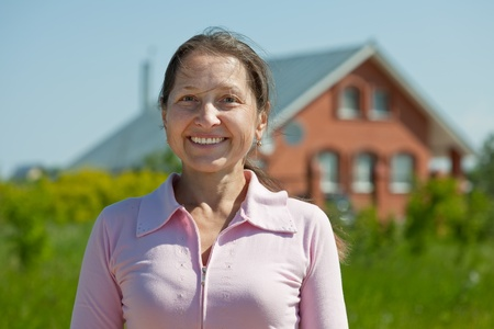 Happy  mature woman  against her home photo