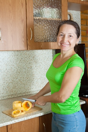 farci:  woman slicing vegetable marrow  on cutting board in her kitchen. See in series stages of cooking of stuffed vegetable marrow