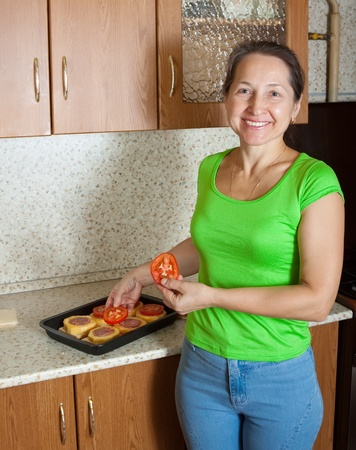 cocozelle: Woman adds tomato on stuffed vegetable marrow. See in series stages of cooking of stuffed vegetable marrow