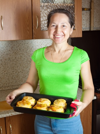 Woman with   roasted stuffed vegetable marrow. See in series stages of cooking of stuffed vegetable marrow  photo