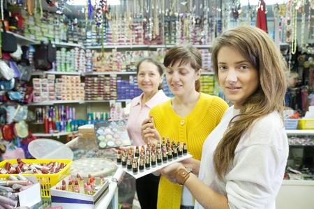 Three women chooses   lipstick at cosmetics  shop photo