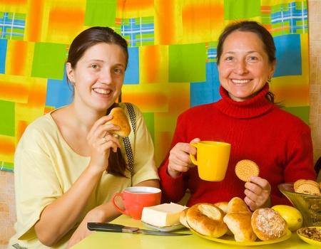 Two smiling women having tea in kitchen Stock Photo - 12601969