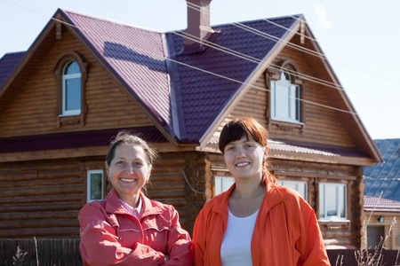 Outdoor portrait of two happy women against real estate Stock Photo - 12601996