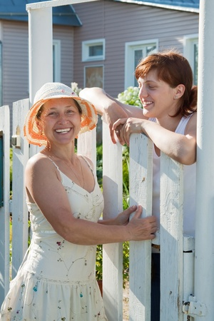 Two happy women near fence wicket  in front of home photo