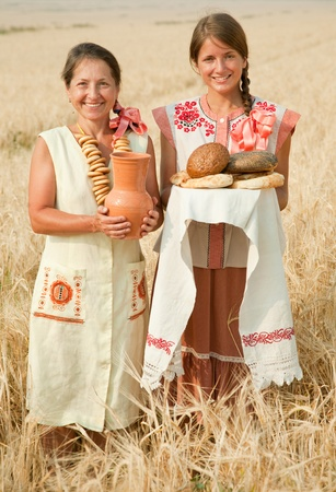 russian food: Women in traditional clothes with bread at cereals field Stock Photo