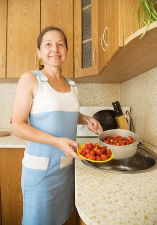 Woman washing strawberries in the kitchen sink photo