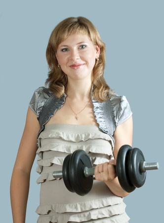 gym dress: Young woman in dress exercising with barbell