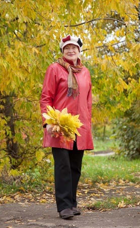Full length shot of mature woman  in autumn park photo