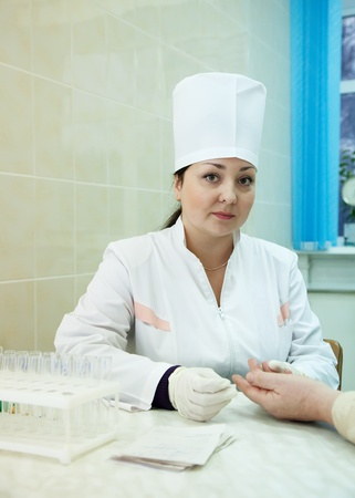 Nurse taking blood sample  from patient in clinic Stock Photo - 12601555