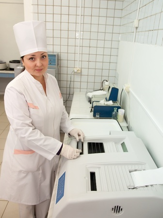 Doctor working with Biochemistry Analyzer in medical clinic
