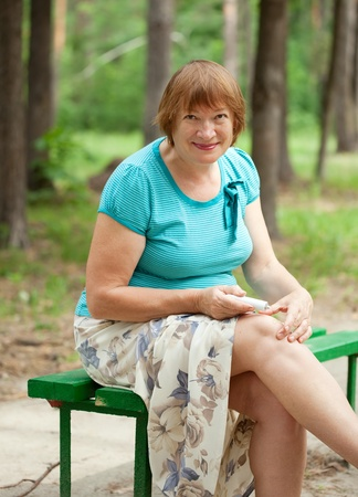 Mature woman embrocating jel in  injury knee Stock Photo - 12601515