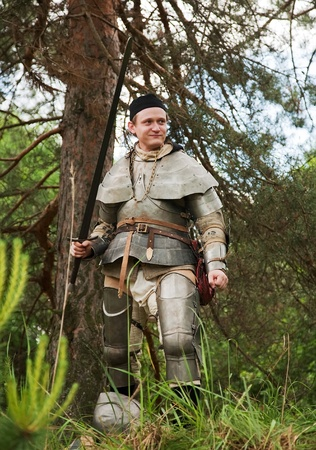 Knight in armor, ready for confrontation at forest in sunny day Stock Photo - 12791089