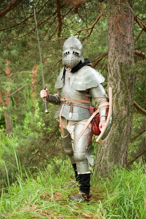 Knight in armour end of XV age in pine forest photo