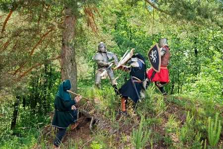 History battle. Few knights in armor is fighting  at forest photo