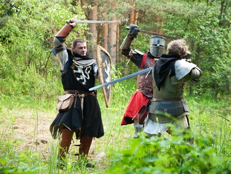three knights in armor is fighting  at forest photo