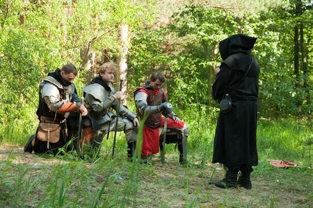 chaplain: Pray of knights in medieval armors before chaplain