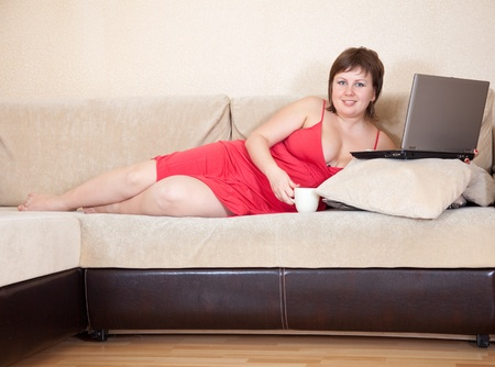 Relaxed woman lying on sofa in livingroom with laptop photo