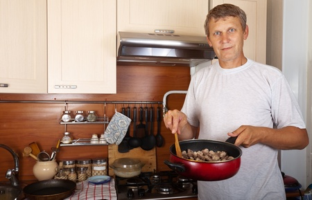 Man cooks meat in home kitchen photo