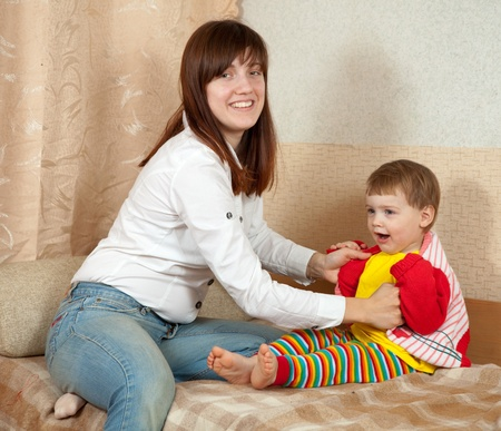 mother dresses her daughter at home Stock Photo - 12793166