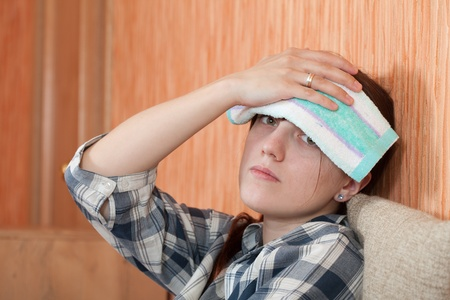 Suffering girl stupes  towel to her head Stock Photo