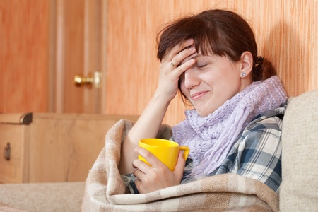 Young illness woman drinking hot tea in blanket photo
