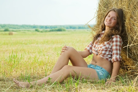 farm girl: Pretty girl in checked shirt resting on straw bale Stock Photo