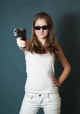 Long-haired  girl in sunglasses aiming a black gun photo