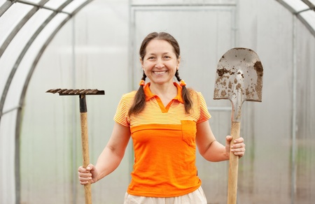 Mature gardener with spade and rake in greenhouse