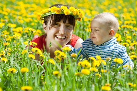 Happy mother and baby laying on dandelion meadow photo