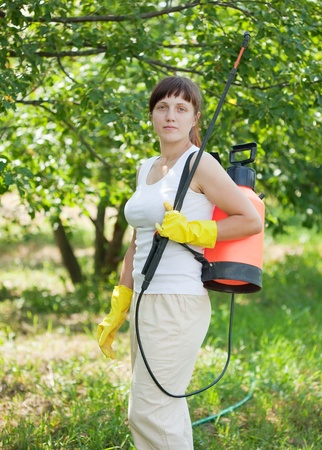 working woman with garden spray  in orchard Stock Photo - 12791291