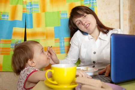 businesswoman feeding baby and  speak by mobile at kitchen in morning photo