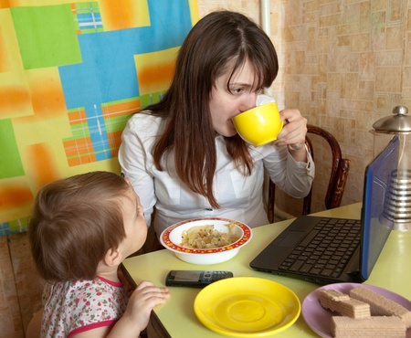 Mother feeding baby and  using  latop at kitchen in morning photo