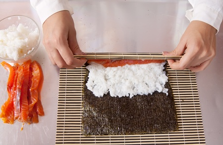 Closeup of cook making  Japanese sushi rolls  with salmon photo