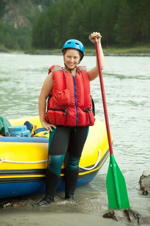 Girl with  paddle near raft at mountain river photo