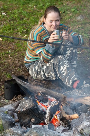 Female tourist drinking tea  at camp near fire photo