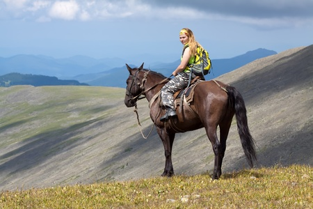 Rider femminile con zaino a cavallo alle montagne photo