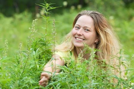 Happy woman with fresh hemp    at cannabis plant photo