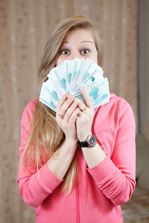 roubles:  happy casual girl with many  roubles  in home interior