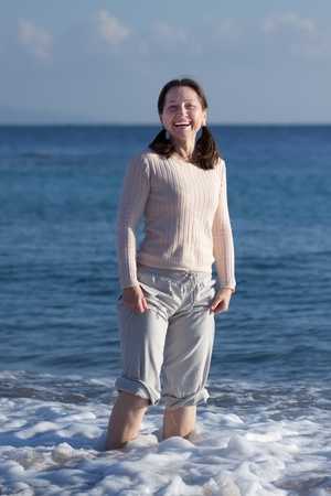 Happy mature woman stands at sea wave Stock Photo - 13024264
